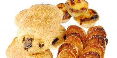nice assortment of pastries (pastel de nata, pain au chocolat and palmier) isolated on white background
