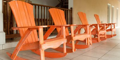 row of orange wooden rocking chairs on a porch (usual setting on a tropical resort)
